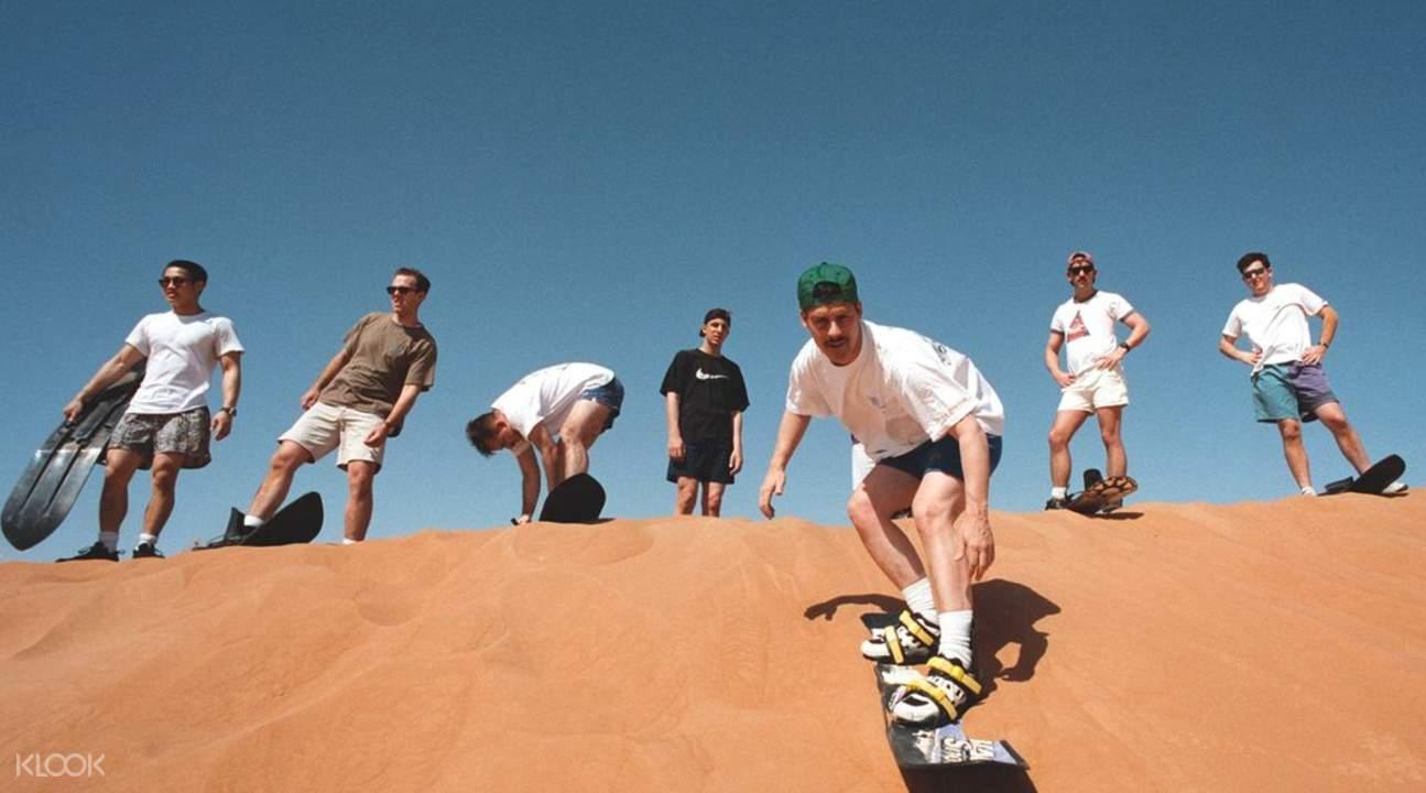 men sandboarding during the evening desert safari